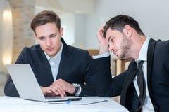 Dos hombres de negocios acertados ooking para una solución Foto de archivo libre de regalías