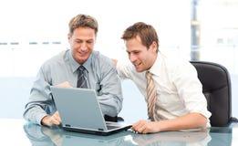Dos hombres de negocios alegres que trabajan junto en una computadora portátil Foto de archivo libre de regalías