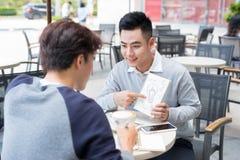 Dos hombres de negocios asiáticos alegres que discuten con los documentos Imagen de archivo libre de regalías