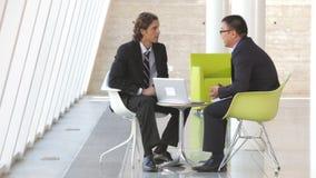 Dos hombres de negocios con el ordenador portátil que tiene reunión almacen de metraje de vídeo