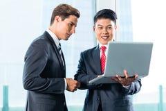 Dos hombres de negocios con horizonte del ordenador portátil y de la ciudad Fotos de archivo