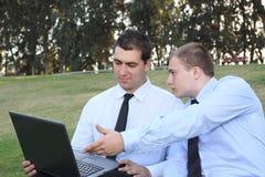 Dos hombres de negocios con la computadora portátil Imágenes de archivo libres de regalías