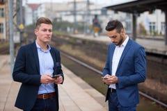 Dos hombres de negocios con los teléfonos que esperan en la estación de tren Imágenes de archivo libres de regalías