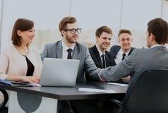 Dos hombres de negocios confiados apretón de manos y sonrisa mientras que se sienta en la tabla así como sus colegas imagen de archivo libre de regalías