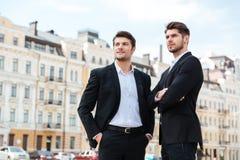 Dos hombres de negocios confiados que se colocan al aire libre Imagenes de archivo
