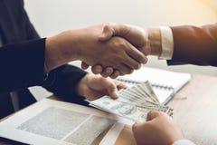 Dos hombres de negocios corporativos que sacuden las manos mientras que un hombre que da el dinero y recibir el efectivo sucio en imagen de archivo libre de regalías