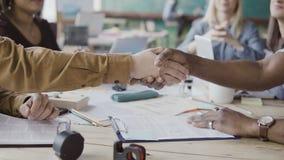 Dos hombres de negocios de los socios, africanos y caucásicos sacuden las manos Grupo de personas que aplaude en un fondo en la o Imágenes de archivo libres de regalías