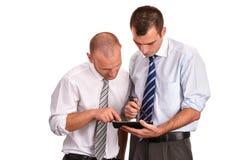 Dos hombres de negocios en camisas, mirando abajo con confianza y contra Imagen de archivo libre de regalías