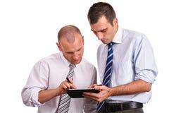 Dos hombres de negocios en camisas, mirando abajo con confianza y contra Imagenes de archivo