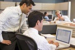 Dos hombres de negocios en el cubículo que mira la computadora portátil Foto de archivo libre de regalías