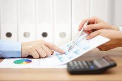 Dos hombres de negocios en la reunión analizan informe financiero y los di