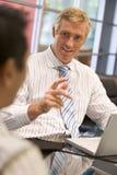 Dos hombres de negocios en la sala de reunión con hablar de la computadora portátil Imagen de archivo libre de regalías