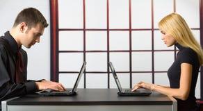 Dos hombres de negocios en las computadoras portátiles Fotos de archivo libres de regalías
