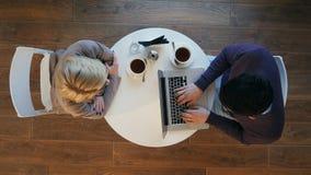 Dos hombres de negocios en un funcionamiento del restaurante, hombre que usa el ordenador portátil, café de consumición de la muj foto de archivo
