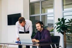Dos hombres de negocios en una reunión de negocios que discuten gráficos foto de archivo