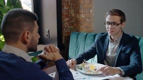 Dos hombres de negocios están hablando durante el almuerzo de negocios, sentándose en la tabla en café almacen de video