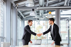 Dos hombres de negocios felices que colocan y que sacuden las manos en la reunión de negocios imagenes de archivo