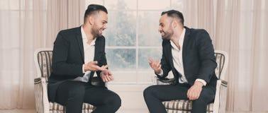 Dos hombres de negocios felices que discuten en la reunión sobre el fondo de la ventana fotos de archivo libres de regalías