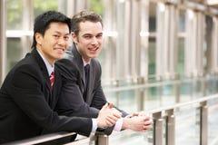 Dos hombres de negocios fuera de la oficina moderna Imagen de archivo libre de regalías
