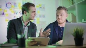 Dos hombres de negocios jovenes discuten el proyecto del negocio almacen de metraje de vídeo
