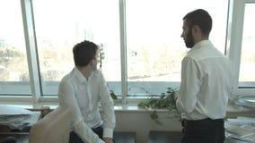 Dos hombres de negocios jovenes están mirando hacia fuera la ventana que discuten la construcción de edificios almacen de metraje de vídeo