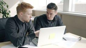 Dos hombres de negocios jovenes que discuten las ideas del proyecto de inicio que se sientan en la tabla con el ordenador portáti almacen de video