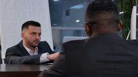 Dos hombres de negocios jovenes que discuten proyecto en la reunión fotografía de archivo