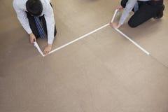 Dos hombres de negocios jovenes que graban encima del piso en la oficina Foto de archivo
