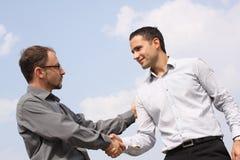 Dos hombres de negocios jovenes que sacuden las manos Imagen de archivo libre de regalías