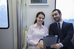 Dos hombres de negocios jovenes que sientan y que miran una tableta digital en el subterráneo Fotografía de archivo
