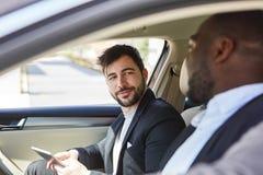Dos hombres de negocios junto en el coche fotos de archivo