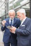 Dos hombres de negocios mayores serios que miran una situación de la tableta delante de un edificio de oficinas imagen de archivo