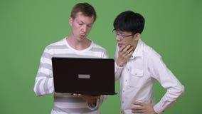 Dos hombres de negocios multi-étnicos jovenes que tienen reunión con el ordenador portátil junto almacen de video