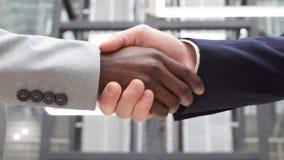 Dos hombres de negocios multinacionales del apret?n de manos Saludo de concepto del trato Hombres de negocios multiculturales que almacen de metraje de vídeo