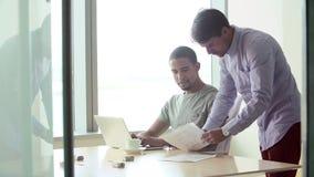 Dos hombres de negocios ocasional vestidos que trabajan en oficina metrajes