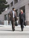 Dos hombres de negocios que caminan en la calle de la ciudad imagenes de archivo