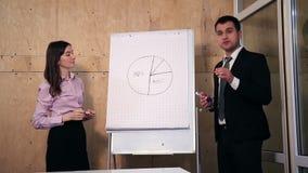 Dos hombres de negocios que dan la presentación en la oficina almacen de video