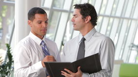 Dos hombres de negocios que discuten el documento en oficina almacen de metraje de vídeo