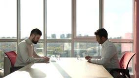 Dos hombres de negocios que firman el acuerdo y el apretón de manos de la sociedad metrajes