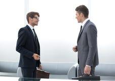 Dos hombres de negocios que hablan la colocación en la oficina foto de archivo libre de regalías
