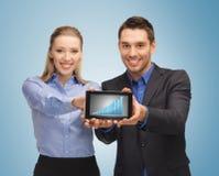 Dos hombres de negocios que muestran la PC de la tableta con el gráfico Foto de archivo libre de regalías