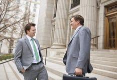 Dos hombres de negocios que ríen junto Imagen de archivo libre de regalías