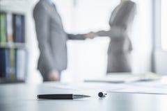 Dos hombres de negocios que sacuden las manos en el fondo, pluma que miente en la tabla en el primero plano Imagenes de archivo