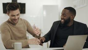 Dos hombres de negocios que sacuden las manos en la cocina abierta Socios felices que discuten ideas almacen de metraje de vídeo