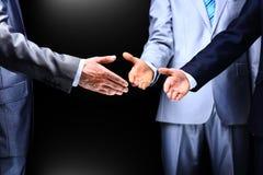 Dos hombres de negocios que sacuden las manos a su líder, Foto de archivo libre de regalías