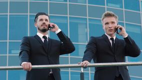 Dos hombres de negocios que se colocan cerca de la barandilla y que hablan en el teléfono metrajes