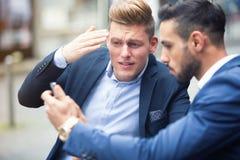Dos hombres de negocios que se colocan exteriores y que miran el teléfono Fotografía de archivo libre de regalías