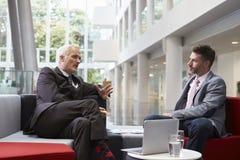 Dos hombres de negocios que se encuentran en área del pasillo de la oficina moderna foto de archivo