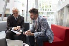 Dos hombres de negocios que se encuentran en área del pasillo de la oficina moderna Fotografía de archivo libre de regalías