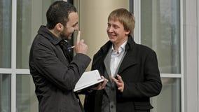 Dos hombres de negocios que se encuentran fuera del edificio de oficinas, sonriendo Fotografía de archivo libre de regalías